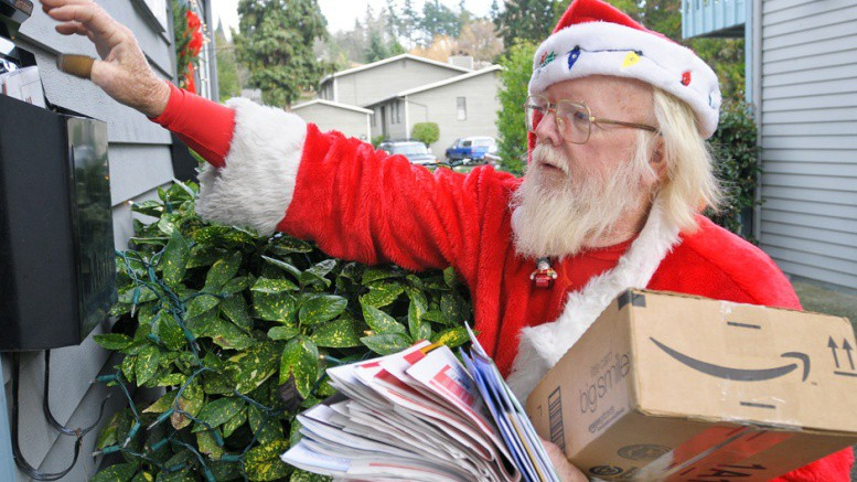 Postal carrier Bob McLean gets into the Christmas spirit along as Santa as he completes his route along 102nd Avenue SE in Bellevue on Wednesday.